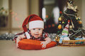 Baby in a cap of santa claus christmas tree and Royalty Free Stock Image