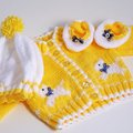 Baby cardigan with hat and shoes babys knitted yellow white scotty dog design along against a plain background Royalty Free Stock Photo