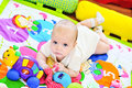 Baby on the carpet with toys Stock Images
