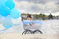 Baby in carriage a boy sitting inside a antique attached to helium balloons Royalty Free Stock Photos