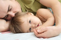 Baby child ailing with father lying together holding hand Stock Image