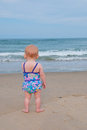 Baby Child on Beach Stares at Ocean Royalty Free Stock Photos