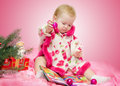 Baby with christmas toys fir branch and book Royalty Free Stock Photo