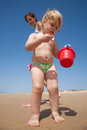 Baby collecting sea shells in red bucket Royalty Free Stock Photo