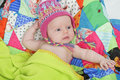 Baby with colorful hat and quilt Stock Images