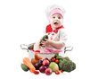 Baby cook girl wearing chef hat with fresh vegetables and fruits Royalty Free Stock Photo
