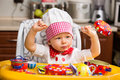 Baby cook girl wearing chef hat in kitchen. Royalty Free Stock Photo