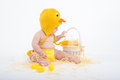 Baby in a costume of chicken looking intently in white wicker basket with hay Royalty Free Stock Photo