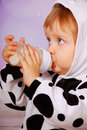 Baby in cow costume drinking milk from bottle Royalty Free Stock Images