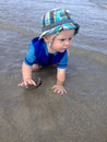 Baby crawling through ocean water at the beach wearing a wetsuit Royalty Free Stock Photo