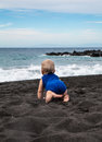 Baby crawling on Playa la Arena black volcanic sand beach Royalty Free Stock Photo