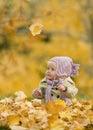 Baby in de herfstbladeren Stock Foto's