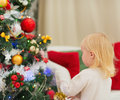 Baby decorating Christmas tree. Rear view Royalty Free Stock Photos