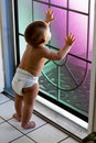 Baby in diaper looks out screen door Royalty Free Stock Photography