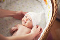 Baby dress mom puts joyful lying in a wicker cradle Royalty Free Stock Image