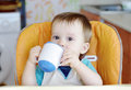 Baby drink from baby cup age of year Royalty Free Stock Photo