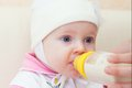 Baby is drinking milk from bottle studio shot Stock Images