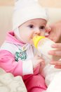 Baby is drinking milk from bottle studio shot Royalty Free Stock Photos