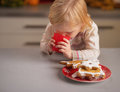 Baby drinking milk and plate with homemade christmas cookies Royalty Free Stock Photo