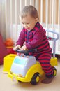 Baby drives baby car at home Stock Photo