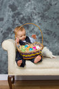 Baby with easter basket happy playing eggs in studio Stock Image