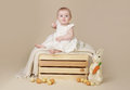 Baby with easter bunny and eggs beautiful sitting up on a a blanket Royalty Free Stock Image