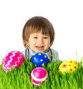 Baby with easter eggs cute boy hunting for colorful hidden in the green grass close up face portrait studio shot over white Royalty Free Stock Images