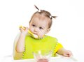 Baby eating with appetite sitting at table isolated Stock Images