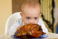 Baby eating a big grilled chicken Royalty Free Stock Photography