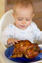 Baby eating a big grilled chicken Stock Images