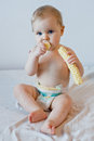 Baby eating crisps at home dressed in a diaper Stock Images