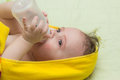 Baby eats from a bottle the while lying Stock Photo