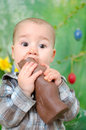 Baby eats chocolate bunny boy is eating a big Royalty Free Stock Photos
