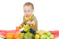 Baby eats fruit on a white background Royalty Free Stock Photo