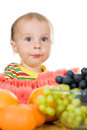 Baby eats fruit on a white background Royalty Free Stock Photos