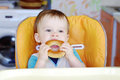 Baby eats round cracknel funny boy age of year eating on kitchen Royalty Free Stock Image