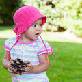 Baby expression little girl holding a pinecone surprised face outdoor picture Stock Image