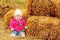 Baby in fall time girl sitting near the hay Stock Image