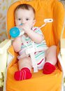 Baby with feeding bottle sitting on highchair age of months Stock Image