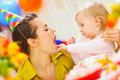 Baby feeding mother with birthday cake Royalty Free Stock Photography
