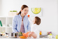 Baby feeding mother with carrot at home kitchen Royalty Free Stock Photo