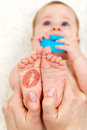 Baby feet with lipstick kiss mark held in woman hands shallow depth Stock Image