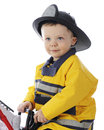 Baby fire fighter close up image of an adorable toddler boy dressed as a fireman on a white background Stock Photos