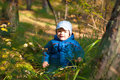 Baby in forest beautiful happy little sitting under trees sunny Royalty Free Stock Images