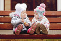 Baby friends on bench sitting the Stock Photos