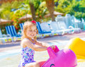 Baby girl in aquapark happy having fun swimming the pool on pink inflatable toy daycare summertime Stock Images