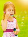 Baby girl blowing soap bubbles closeup portrait of cute outdoors playing game on spring garden sunny day happy childhood concept Royalty Free Stock Photo