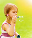 Baby girl blowing soap bubbles closeup portrait of cute in spring park having fun outdoors happy childhood concept Stock Photos