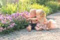 Baby girl and boy sitting in a beautiful garden and pointing to purple flower Royalty Free Stock Photo