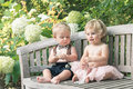 Baby girl and boy sitting on wooden bench and looking on bead Royalty Free Stock Photo